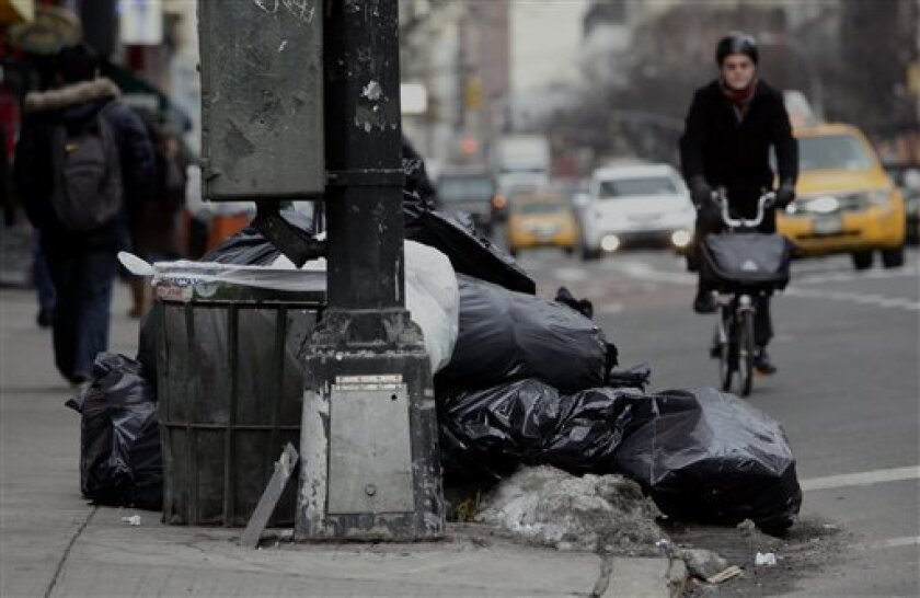 Uncollected garbage overflow the sidewalk and onto 3rd Avenue on Thursday, Jan. 6, 2011, in mid-Manhattan, New York. Another storm is being forecast for New York City, where Mayor Michael Bloomberg is still under fire for slow cleanup of last week's blizzard that kept streets clogged for days and delayed trash pickups. (AP Photo/Bebeto Matthews)