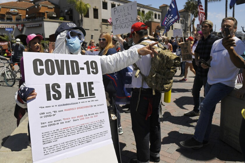 Protesters demonstrate in Huntington Beach on April 17 against stay-home orders that were put in place due to the COVID-19 pandemic.