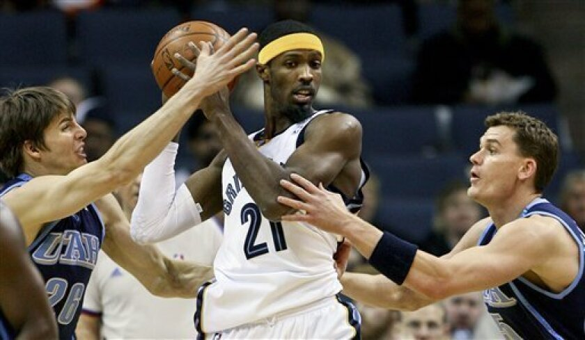 Memphis Grizzlies forward Hakim Warrick (21) gets double-teamed by Utah Jazz forward Kyle Korver (26) and forward Matt Harpring (15) during the first half of an NBA basketball game Friday, Jan. 16, 2009, in Memphis, Tenn.  (AP Photo/Lance Murphey)