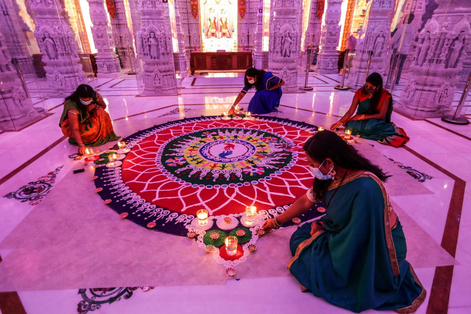Women in traditional robes kneel around an intricate work of sand art inside a Hindu temple
