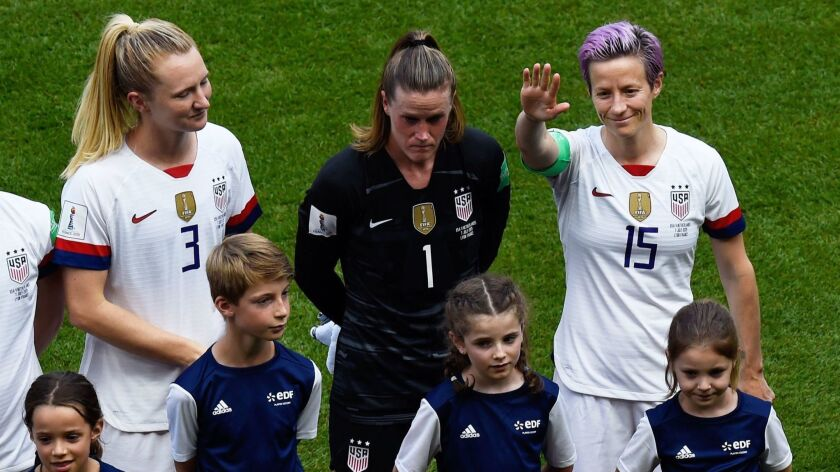 U.S. forward Megan Rapinoe waves while standing next to teammates Samantha Mewis, far left, and Alyssa Naeher before the start of the Women's World Cup final against the Netherlands in Lyon, France, on Sunday.