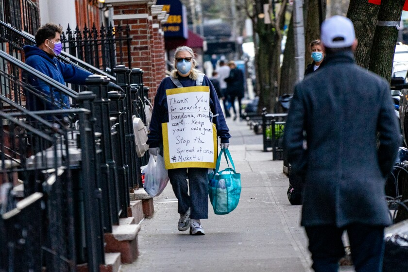 A pedestrian wears a sign thanking people for wearing face coverage in New York City on Wednesday.