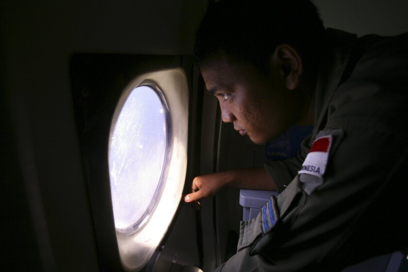 An Indonesian Navy crew member scans the water bordering Indonesia, Malaysia and Thailand during a search operation for the missing Malaysian Airlines Boeing 777 near the Malacca straits on Monday, March 10, 2014. Dozens of ships and aircraft have failed to find any piece of the missing Boeing 777