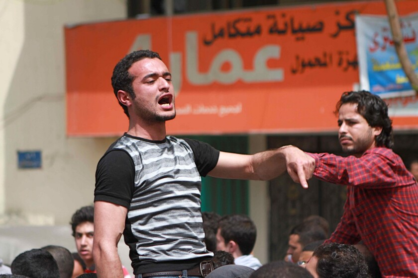 In this April 1, 2011, photo, activist Ahmed Douma chants slogans during a march to Cairo's Tahrir Square demanding the prosecution of members of former President Hosni Mubarak's government. A lawyer for Douma and two other prominent youth activists said his clients were beaten Monday by guards before a hearing in the appeal of their prison sentences.