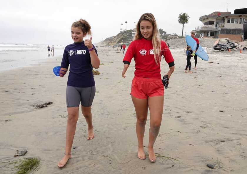Sophia Saunders, 10, of Clairemont, and surfer Liv Stone, 17, walk to surf at Moonlight Beach on June 23.