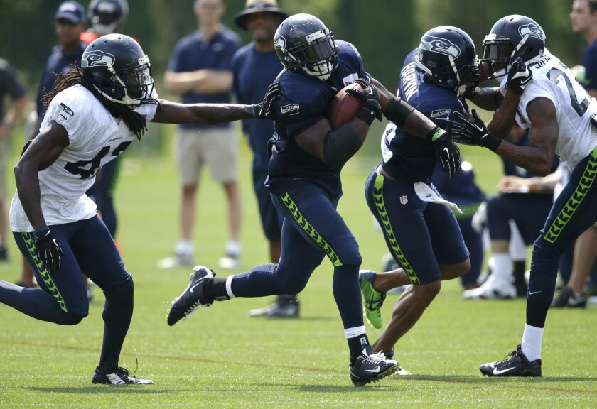 Seattle Seahawks running back Robert Turbin, second from left, carries the ball as wide receiver Percy Harvin, second from right, blocks Tharold Simon, right, and Terrance Parks pursues the tackle at left, during practice drills, Saturday, Aug. 2, 2014, at NFL football training camp in Renton, Wash. (AP Photo/Ted S. Warren)