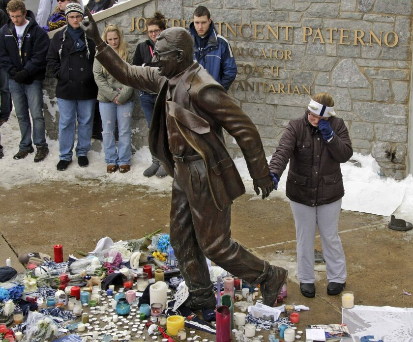 FILE - In this Jan. 22, 2012,  file photo, a woman pays her respects at a statue of former Penn State football coach Joe Paterno outside Beaver Stadium on the Penn State University campus in State College, Pa. More than 200 former Penn State football players are petitioning university leaders to re