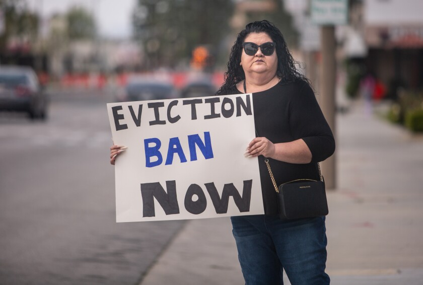"""Irma Zamorano of El Monte holds a placard saying """"Eviction ban now"""" outside El Monte City Hall"""