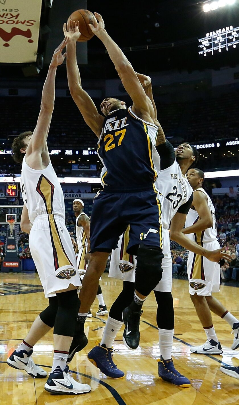 Utah Jazz center Rudy Gobert (27) and New Orleans Pelicans center Omer Asik, left, and forward Anthony Davis (23) go for a rebound during the first half of an NBA basketball game in New Orleans, Wednesday, Feb. 10, 2016. (AP Photo/Tyler Kaufman)