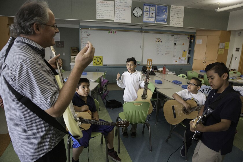 Rock band director Raymond Little, left, conducts practice with students at Carlos Santana Arts Academy