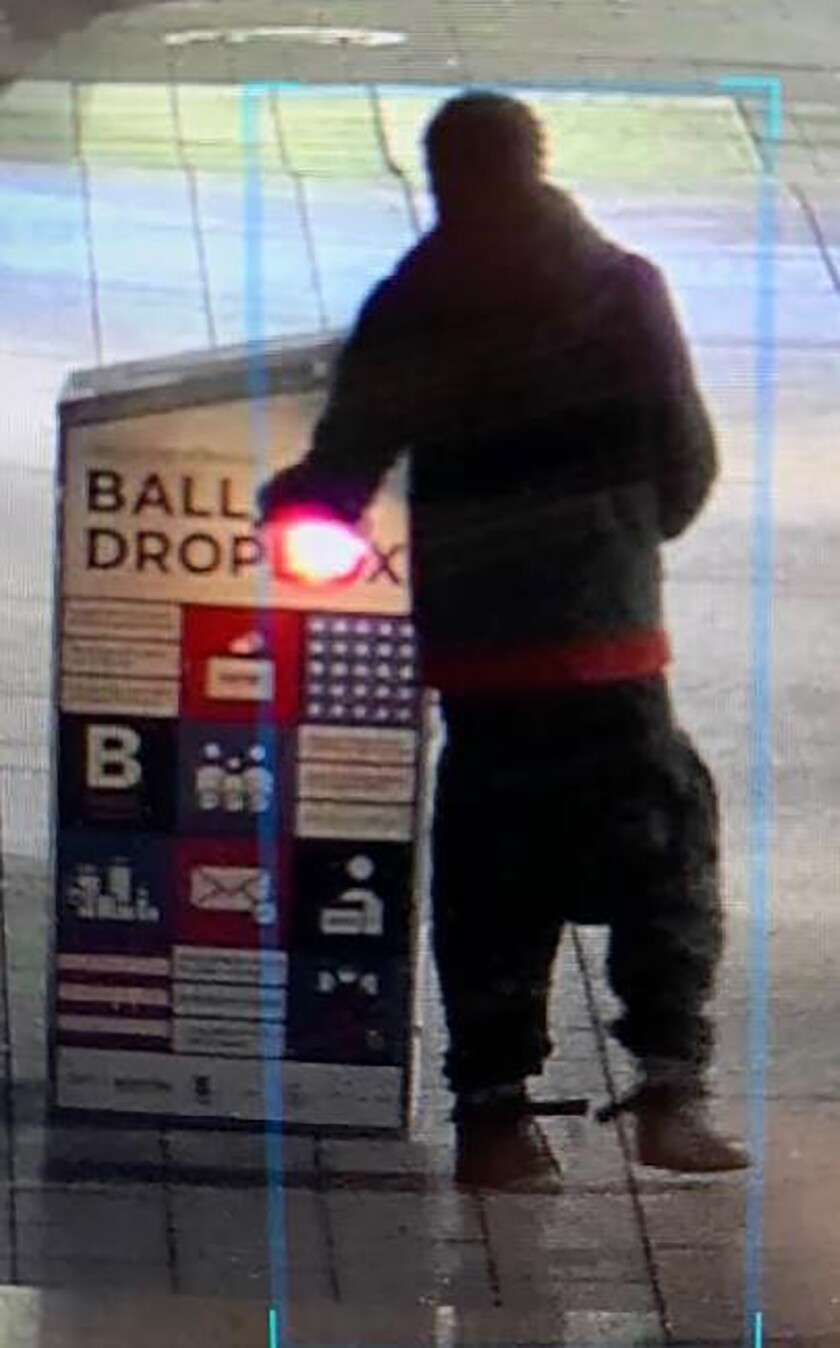 """This surveillance image provided by the Boston Police Department shows a man approaching a ballot drop box outside the Boston Public Library, early Sunday, Oct. 25, 2020, in downtown Boston. Massachusetts election officials say a fire was set at the ballot drop box holding more than 120 ballots in what appears to have been a """"deliberate attack."""" Boston Police say that an arson investigation is underway and the person shown in this surveillance image is a person of interest. (Courtesy of Boston Police Department via AP)"""