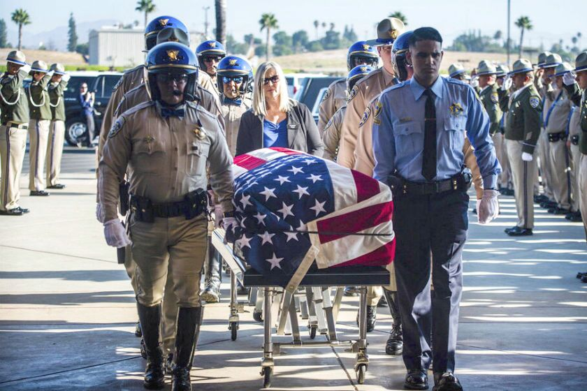 The flag-draped casket of fallen CHP Officer Andre Moye Jr. arrives at Harvest Christian Fellowship Church in Riverside on Tuesday.