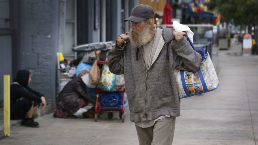 A homeless man walks along University Avenue near Vermont Street in Hillcrest.