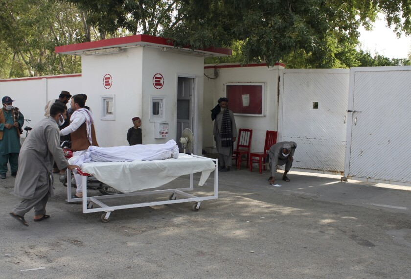 The body of a victim is carried away after an attack June 29 at a busy market in Afghanistan's Helmand province.