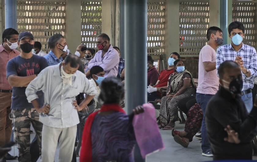People wait for their results of COVID-19 test at a government hospital in New Delhi