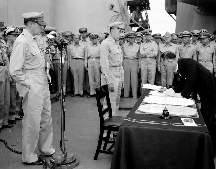 U.S. Gen. Douglas MacArthur, left, watches as Japanese Foreign Minister Mamoru Shigemitsu signs surrender document.