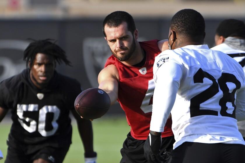 Las Vegas Raiders quarterback Derek Carr (4) hands off the ball torunning back Josh Jacobs (28) during an NFL football practice Wednesday, July 28, 2021, in Henderson, Nev. (AP Photo/David Becker)