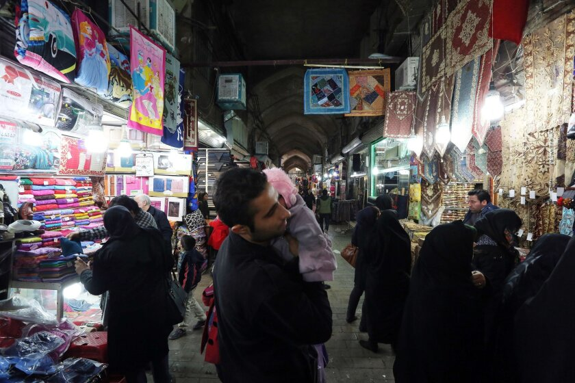 Iranians shop at the main bazaar in Tehran on Thursday. Sanctions have battered Iran's economy, with the inflation rate currently between 17 and 18%.