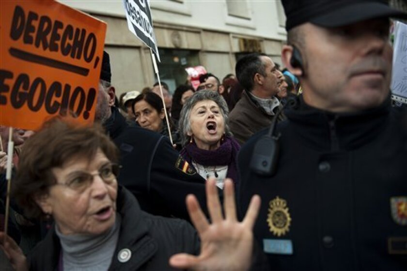 Demonstrators, some of them from the Platform of People Affected by Mortgages, a group campaigning to stop evictions, shout slogans against the government outside the Parliament as the Spanish Parliament considers whether to admit a popular petition to change mortgage laws and halt evictions of tho