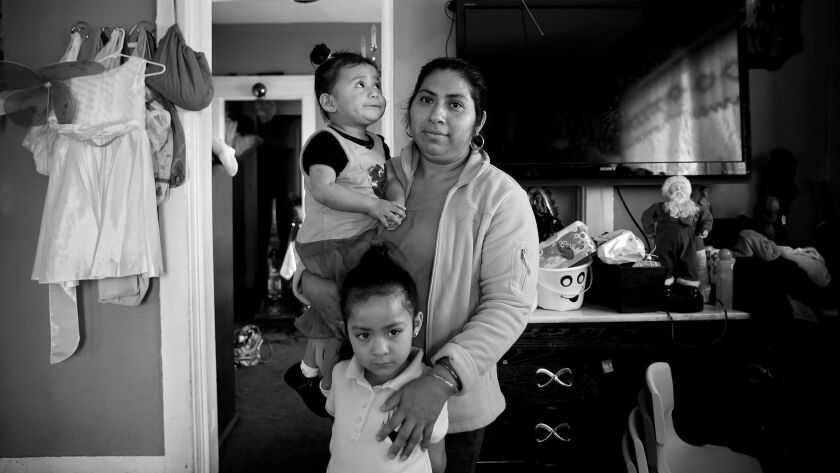 Cornelia Martinez, with some neighborhood children. She and her partner, Freddy Velasquez, have lived in their one-bedroom apartment since 1999 with their two daughters. She says she was pressured to leave after the defendants purchased the building, according to a declaration.