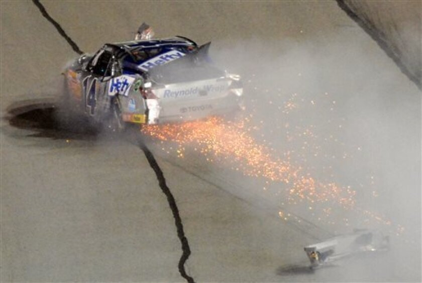 Driver Jeff Green (14) blows an engine and loses a bumper late in the Nationwide Series auto race at Atlanta Motor Speedway, Saturday, Aug. 31, 2013, in Hampton, Ga. (AP Photo/Joe Sebo)