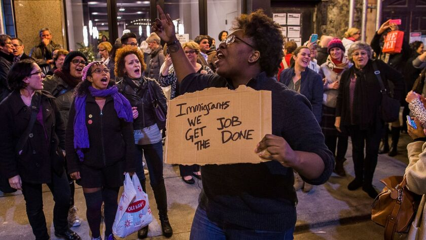 "A protester holds a sign with lyrics from ""Hamilton."" She was part of a group shouting at Vice President-elect Mike Pence as he left the show Friday night."