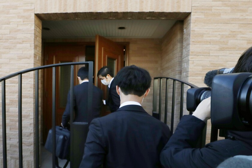 Prosecutors enter the Tokyo home of former Nissan Chairman Carlos Ghosn during a raid Jan. 2.