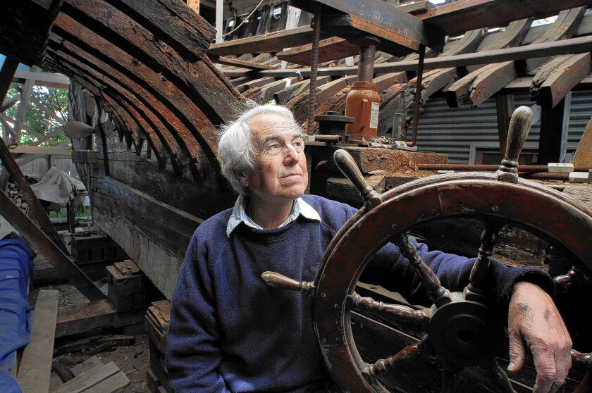 While holding on to the original wheel in 2012, Dennis Holland looks over his rebuilding efforts of the 72–foot Shawnee, parked in between his historic barn and home in Newport Beach. He died Monday in his home. He was 68.