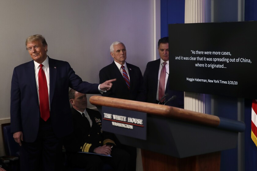 President Donald Trump points as he watches as a White House produced video plays during a briefing about the coronavirus in the James Brady Press Briefing Room at the White House, Monday, April 13, 2020, in Washington.