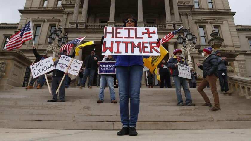 Protesters outside the Michigan Capitol on Wednesday show their displeasure with Gov. Gretchen Whitmer's stay-at-home order. Some of the protesters carried guns.