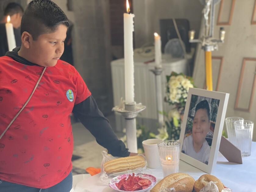 Bryan Osvaldo Hernández, de 10 años, mira en el altar a su hermano Brandon Giovanni Hernández Tapia