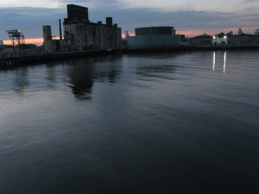 A view of the Brooklyn waterfront at dusk shows industrial buildings in silhouette and the waters of New York Bay