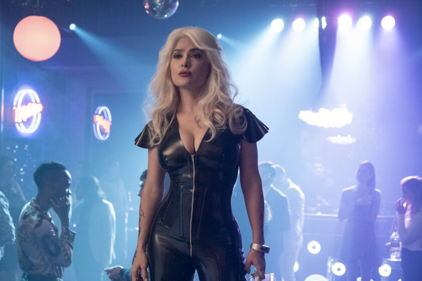 Salma Hayek wears blond hair and a leather jumpsuit in a club setting.