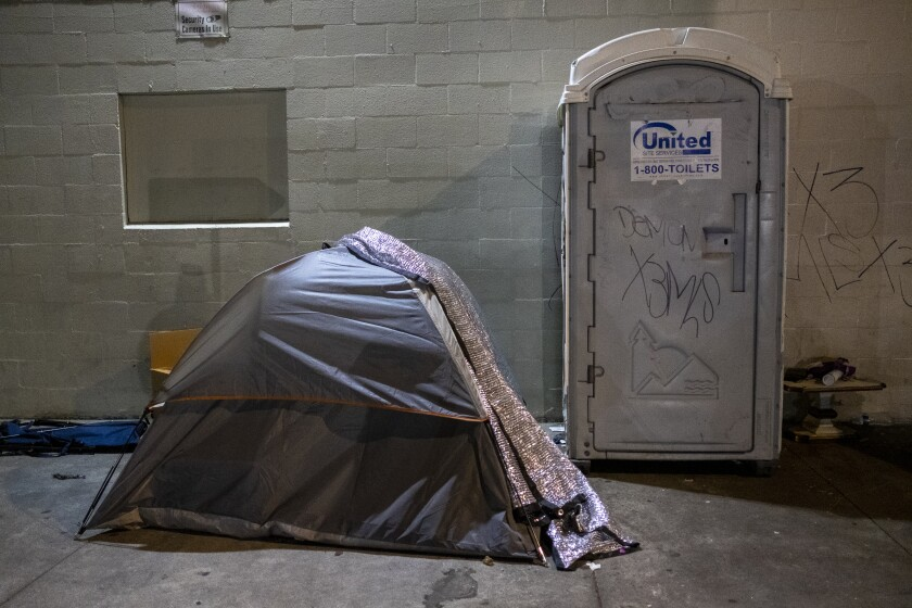 A tent next to a portable toilet on a sidewalk