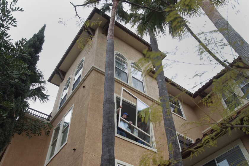 Workers install a window a unit being upgraded at La Mirage apartments overlooking Mission Valley on Tuesday, Feb. 18, 2014.