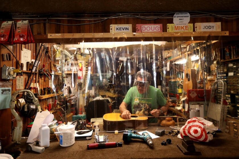 Michael Hawelu, a luthier, repairs guitars at McCabe's Guitar Shop.