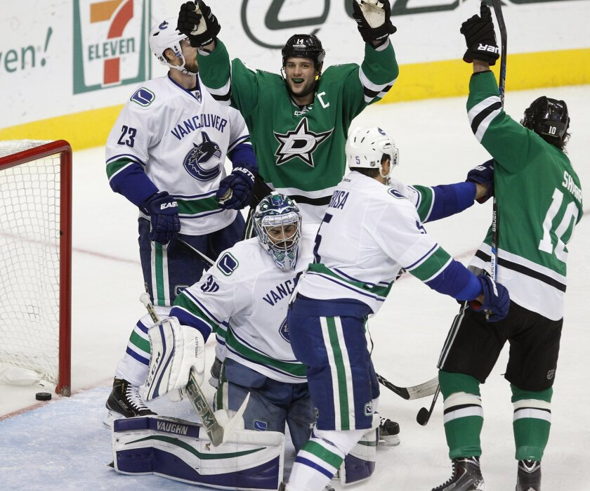 Dallas Stars left wing Jamie Benn (14) celebrates with left wing Patrick Sharp (10) after scoring a goal against Vancouver Canucks goalie Ryan Miller (30) during the first period of an NHL hockey game Friday, Nov. 27, 2015, in Dallas. (AP Photo/Tim Sharp)
