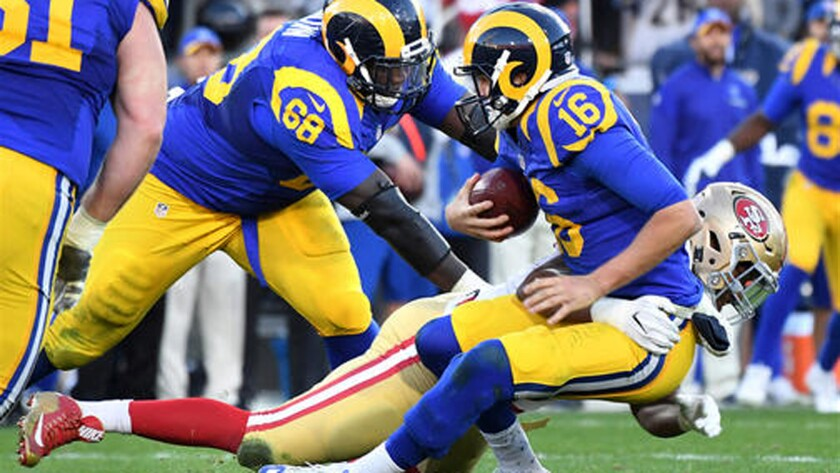 Rams quarterback Jared Goff, wearing the team's throwback uniform, is sacked by 49ers defensive lineman Ronald Blair.