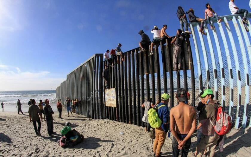 Members of the caravan of Central Americans climb the border wall in Tijuana, State of Baja California, Mexico, Nov. 13, 2018. EPA-EFE / Joebeth Terriquez