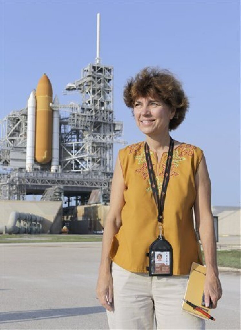 This Wednesday, June 22, 2011 picture shows Associated Press Aerospace Writer Marcia Dunn with the space shuttle Atlantis in the background at a news conference during the Terminal Countdown Demonstration Test at the Kennedy Space Center in Cape Canaveral, Fla., The launch of Atlantis, the final space shuttle mission, is scheduled for July 8, 2011. (AP Photo/John Raoux)