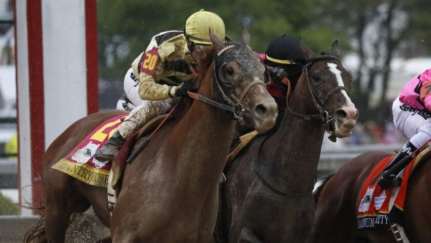 Flavien Prat on Country House, left, races against Luis Saez on Maximum Security, second from right,