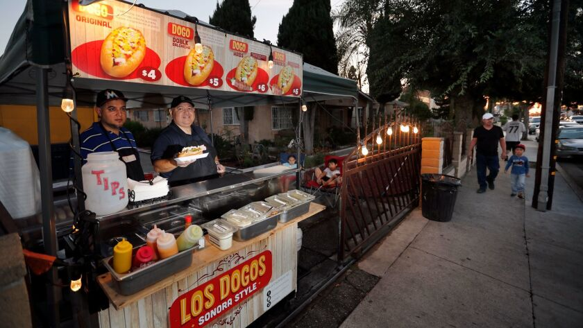 Alejandro Zamorano, right, and his nephew David Zamorano, serve Sonora, Mexico-style hot dogs from their cart in front of a friend's house in Compton.