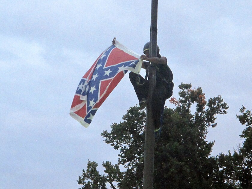 Bree Newsome of Charlotte, N.C., removes the Confederate battle flag at a Confederate monument outside the Statehouse in Columbia, S.C.