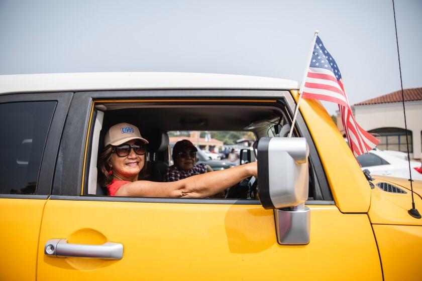 Lou Mendoza, 70, and Amanda Galsim, 62, both registered nurses, attended a flag parade