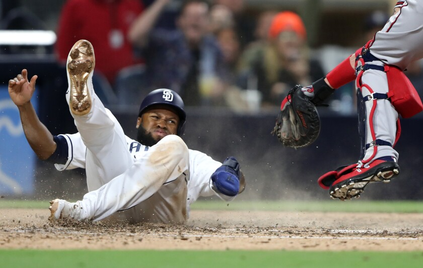 Manuel Margot slides across the plate with a run that gave the Padres a 4-3 lead over the Braves in Saturday's seventh inning.