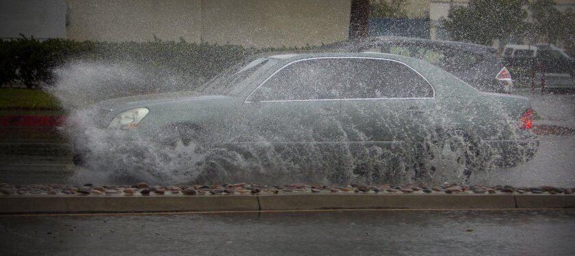 A car is obscured as it drives through a puddle of water along Balboa Avenue in Clairemont Mesa, Tuesday afternoon.