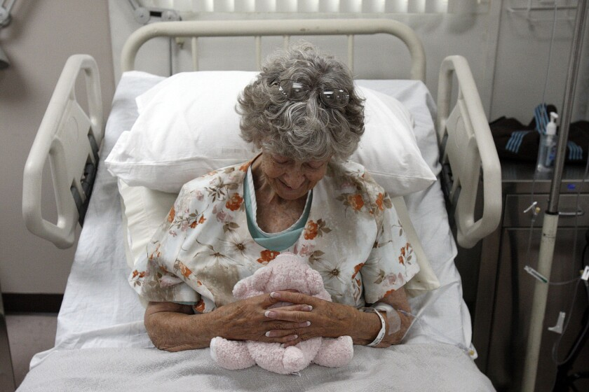 """Jennie Guard, 73, cuddles a stuffed animal during taping of the new television series """"Getting On"""" at St. Luke Medical Center in Pasadena. """"Getting On,"""" a new HBO comedy from the creators of """"Big Love,"""" casts a wry eye on the business of old age and death in an extended-care facility in Long Beach."""