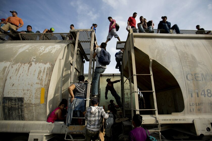 In this July 12, 2014, photo, Central American migrants climb on a north bound train during their journey toward the U.S.-Mexico border, in Ixtepec, Mexico. The number of unaccompanied minors detained on the U.S. border has more than tripled since 2011. Children are also widely believed to be crossing with their parents in rising numbers. (AP Photo/Eduardo Verdugo)