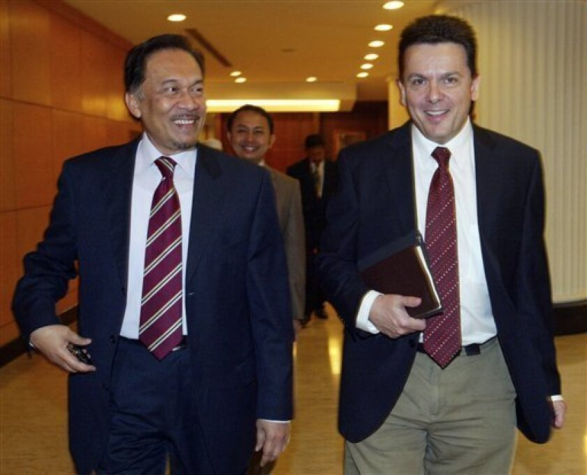 In this Wednesday, Dec. 8, 2010 photo, Australian senator Nick Xenophon, right, walks with Malaysian opposition leader Anwar Ibrahim at the Parliament House in Kuala Lumpur, Malaysia. Authorities on Saturday, Feb. 16, 2013 detained and planned to deport Xenophon who flew into Malaysia to highlight
