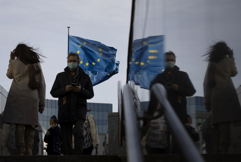 Flags of the European Union flap in the wind as people walk with protective face masks near a set of stairs in front of EU headquarters in Brussels, Tuesday, Feb. 23, 2021. (AP Photo/Virginia Mayo)